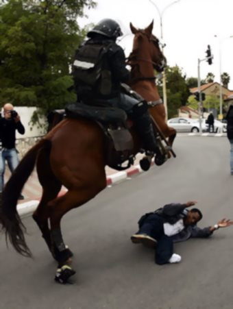 An Ethiopian Jew is knocked down by a mounted police officer during a demonstration in central Jerusalem in 2006