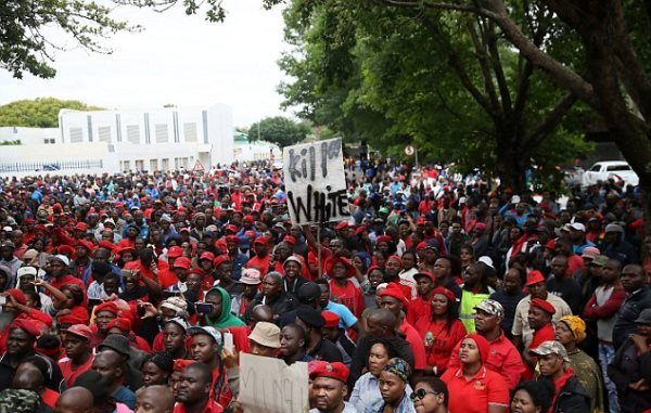 Two white South African farmers who forced a Black man into a coffin and threatened to set him alight are facing Christmas in custody amid fears their release would spark a race riot. More than 400 protestors, held back by a line of police, called for 'reveng